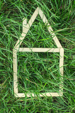 Model house made of wooden sticks on green grass photo