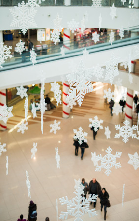 Blurred people in shopping center on christmass. Snowflakes photo