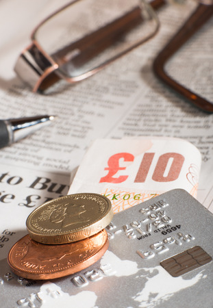 Glasses, coins, credit cards and banknotes on newspaper.Macro shot photo
