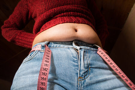 Woman showing fat belly. Pink tape measure photo