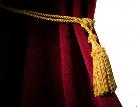 Red velvet curtain with tassel. Close up white isolated curtain photo