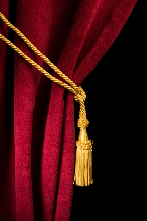 Red velvet curtain with tassel. Close up black isolated curtain photo
