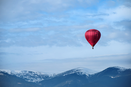Red balloon in the blue cloudy sky