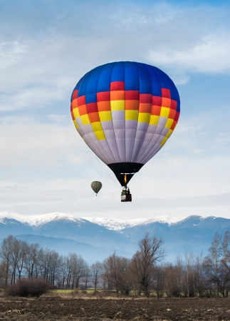 Multicolored Balloon in the blue cloudy sky.  photo