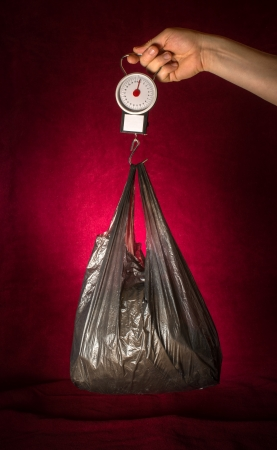 Weigh scales and bag on red background. Stock Photo