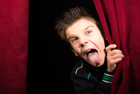 naughty woman: Child stick out his tongue.Appearing beneath the curtain