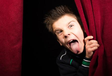 Kinderen steken zijn tongue.Appearing onder het gordijn
