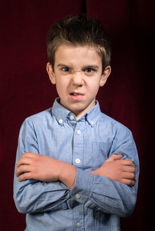 Frowning boy in blue shirt on red background photo