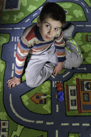 Child is playing with cars on carpet. photo