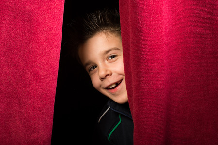 appearing: Child appearing beneath the curtain. Red curtain.