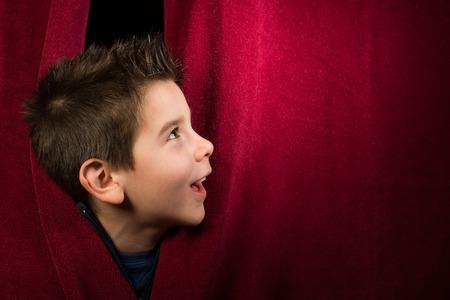Kind te zien zijn onder het gordijn. Rode gordijn.