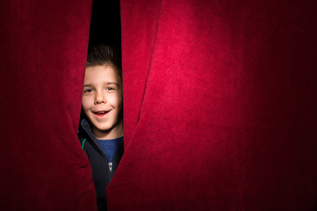 appear: Child appearing beneath the curtain. Red curtain.