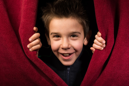 stage performance: Child appearing beneath the curtain. Red curtain.
