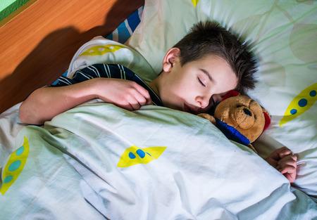 Slapen kind met zijn stuk speelgoed draagt. Stockfoto