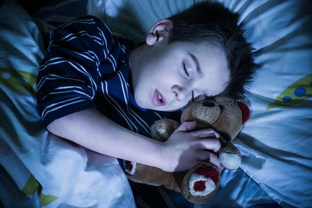 Slapende kind met zijn speelgoed beer.