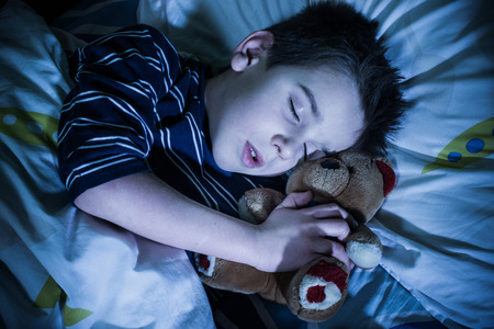american children: Sleeping child with his toy bear.