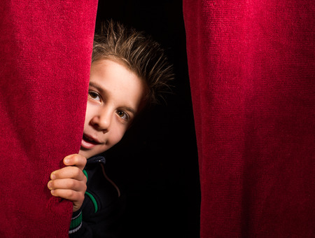blind child: Child appearing beneath the curtain. Red curtain.