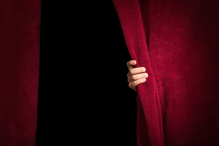 theatre performance: Hand appearing beneath the curtain. Red curtain.