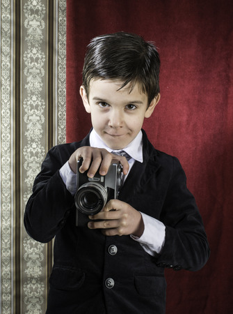 Boy with vintage camera. Vintage clothes Stock Photo - 26312641