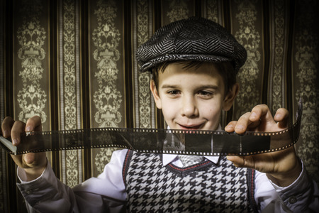 Child considered analog photographic film. Vintage clothes and background Stock Photo - 26312646