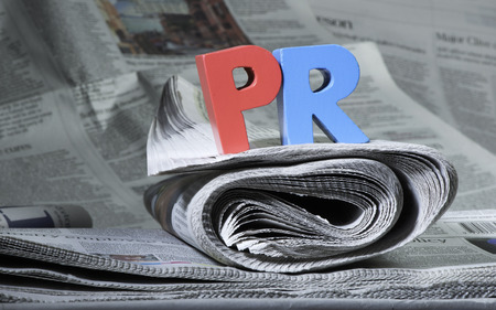 Word PR on newspaper. Wooden letters photo