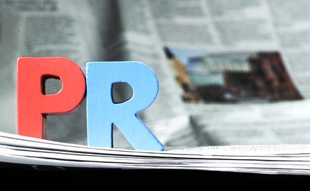 relaciones publicas: PR Palabra en el periódico. Letras de madera Foto de archivo