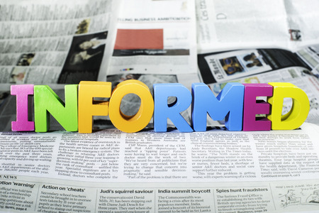 inform: Word informed on newspaper. Wooden letters Stock Photo
