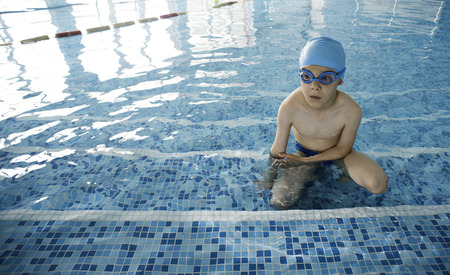 Little boy in swimming pool. Blue swimming pool. photo