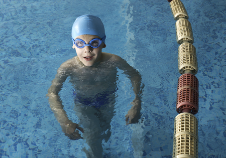 Little boy in swimming pool. Blue swimming pool. Stock Photo - 28224537