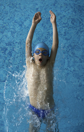 Child swimmer in swimming pool. Blue color swimming pool photo