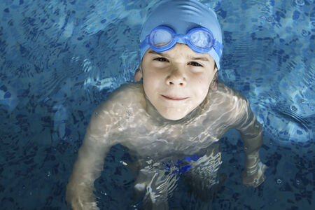 Little boy in swimming pool. Blue swimming pool. Stock Photo - 28634678