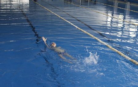 Child swimmer in swimming pool. Blue color swimming pool Stock Photo - 28634687