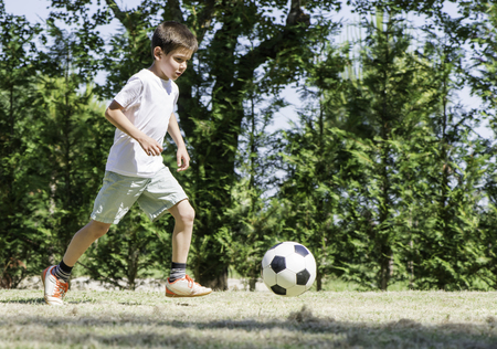 Child playing football in a stadium. Trees on the background Stock Photo - 29893850