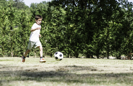 Child playing football in a stadium. Trees on the background Stock Photo - 29893852