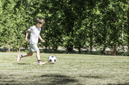 Child playing football in a stadium. Trees on the background Stock Photo - 29893853