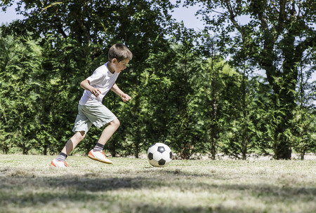 Child playing football in a stadium. Trees on the background Stock Photo - 29893855