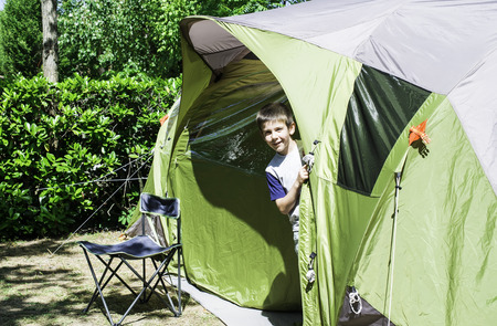 Child peeks from a green tent. Campsite photo