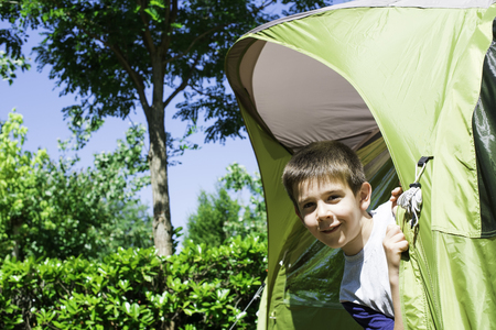 Child peeks from a green tent. Campsite Stock Photo - 29894318