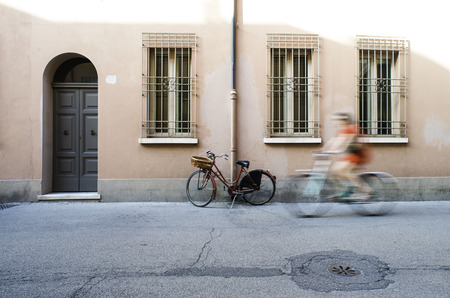 Red old Italian bicycle on sunlight. Ancient buildings photo
