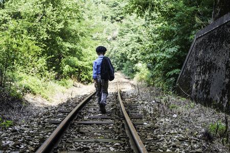 Child walking on railway photo