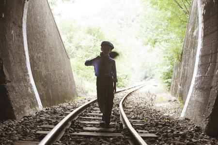 Child walking on railway road with vintage siutcase. photo