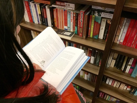 unfold: Women unfold book in a bookstore