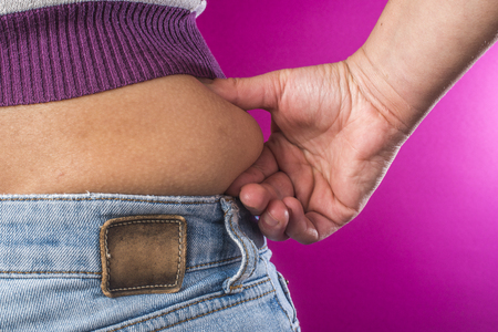 Woman with jeans shows her belly. Overweight. Stock Photo