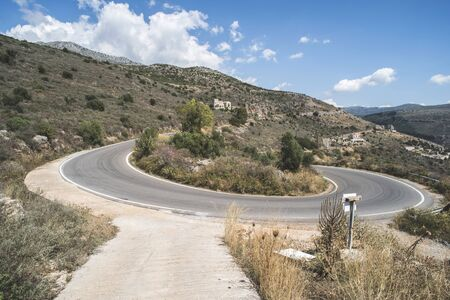 hairpin: Bend in the mountain road. Blue cloudy sky. Greece