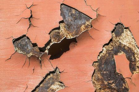 Red cracked paint on rusty iron. Sun light. Bulgaria photo