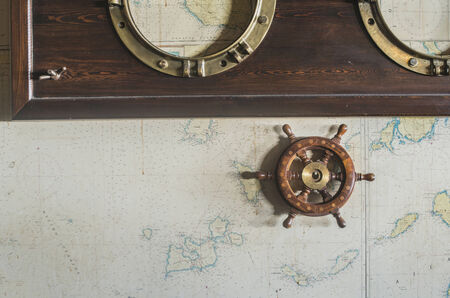 ship porthole: Boat details on wall. Vintage map and rudder. Greece