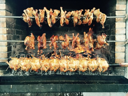 grill: Chickens are roasted on a grill with wood