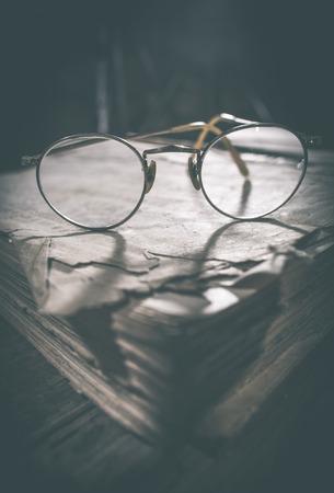 round glasses: Viejas gafas redondas de la vendimia y viejo libro. Luz baja