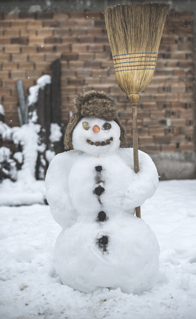 Snowman in the yard holding a broom photo