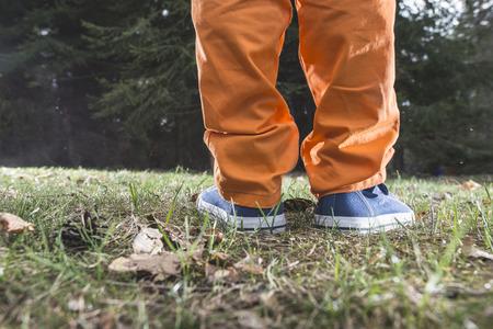 persona caminando: Niño que recorre en el bosque. Cierre para arriba los zapatos Foto de archivo